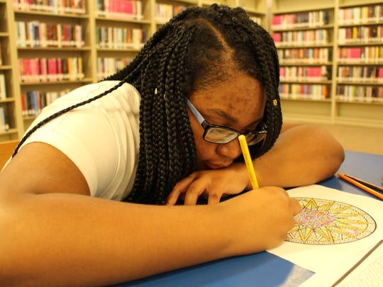 Jenesis Foster, 12, concentrates on her coloring book Saturday morning at the Juliette Hampton Morgan Library.
