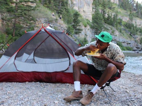 Hiker Kahindo Kamau digs into a pork taco at the mock backcountry kitchen. Kamau said he liked the loaded mashed potatoes the most.