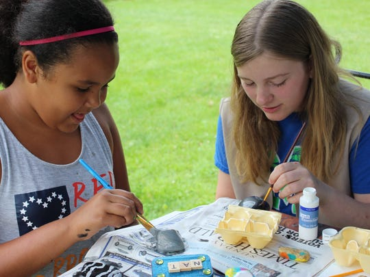 Destiny Sweet, right, and Natalie Thornton paint rocks last week. Girl scouts with the Troop 70611 from Cros-Lex painted roughly 100 rocks.