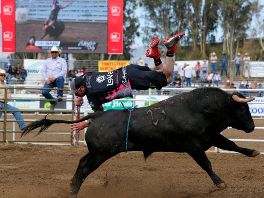 Toby Inman dives over a bull during freestyle bullfighting