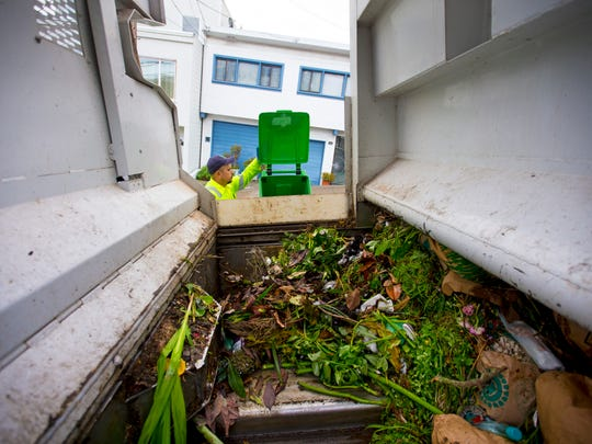Recology Waste Zero employee Arnoldo Picazo collects food scraps and yard trimmings during a curb side pick up in San Francisco. The organic material is then composted and used by local farmers. San Francisco has a Zero Waste initiative by 2020.