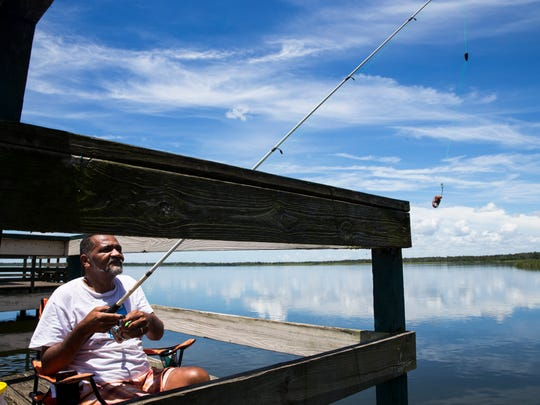 Tony Rosario, of Fort Myers, fishes off the pier at Lake Trafford in Immokalee on Thursday, July 27, 2017. The state has been planting native bulrush weeds to provide better habitat for bass and smaller fish after an effort to rid the lake of an invasive plant killed most of them a few years ago.