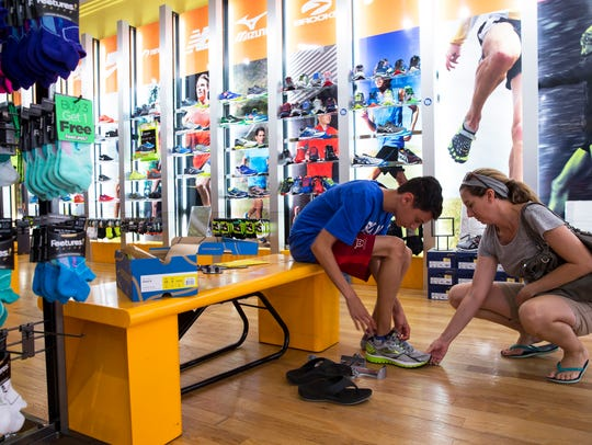 Melissa Bagby helps her son Alex, 13, while shopping