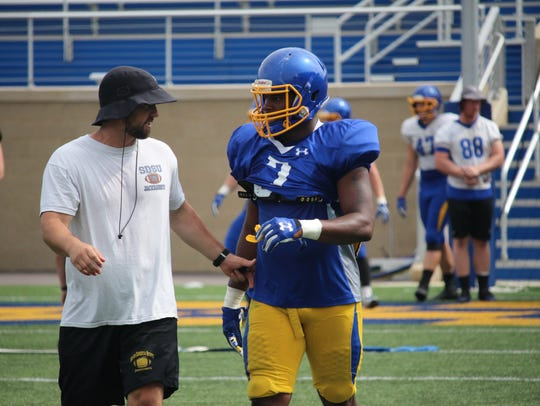 SDSU linebackers coach Jimmy Rogers talks with freshman