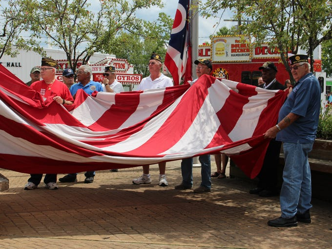 Local veterans hold up an American flag at the Richland