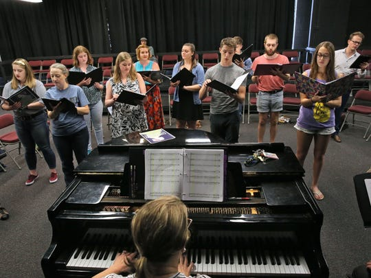 Music director Michelle Klotz plays the piano as singers rehearse the opera.