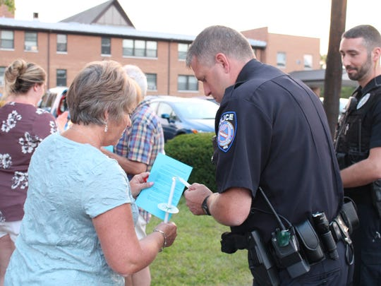 "Jeromesville resident Barb Raudebaugh helps an Ashland police officer light a candle during a vigil  in support of Charlottesville at the Christ United Methodist Church on Monday, Aug. 14, 2017. ""I think change needs to happen so that this doesn't continue to happen and so power isn't given to the wrong ideology,"" Raudebaugh said."