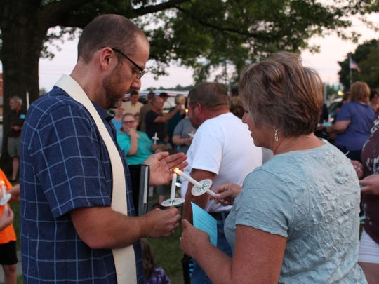 Christ United Methodist Church co-pastor John Priebe helps Jeromesville resident and church administrative assistant Barb Raudebaugh light a candle during a vigil at the church Monday, Aug. 14, 2017. The vigil was held in support of Charlottesville after the weekend's rally and violence in the city.