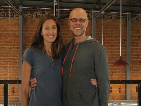 Megan Curtes Korpela and Kevin Korpela smile in the newly remodeled Downtown Grocery loft ahead of the store's opening later this month.