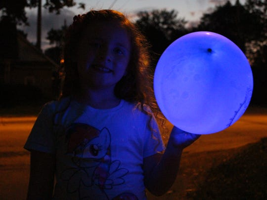Mariah Perrigan, 4, of Bellville poses with her blue glow-in-the-dark balloon during the Blue Lights and Bubbles Parade in August 2017.