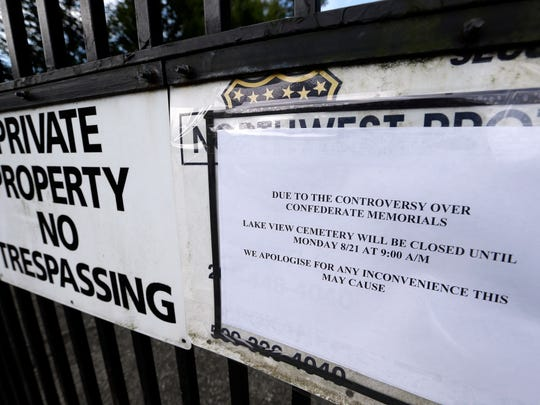 A sign advising closure of the facility is posted on the locked gates of Lake View Cemetery, which was shut following angry messages they've received over a memorial for Confederate soldiers there, Thursday, Aug. 17, 2017, in Seattle. The private cemetery was shut down a day earlier and is expected to remain closed through the weekend over a memorial that's stood there nearly a century and now there's a petition asking for it to come down. The memorial was built with help from the Daughters of the Confederacy 91 years ago. (AP Photo/Elaine Thompson)