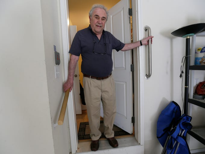 Hand rails help steady Barry Zuckerman, 79, as he steps