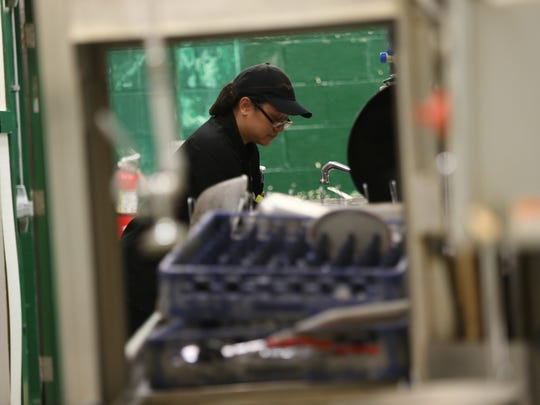 Fatima Ting cleans her equipment after finishing cooking during week 12 at The Culinary School at the Food Bank of Delaware in Newark Wednesday.