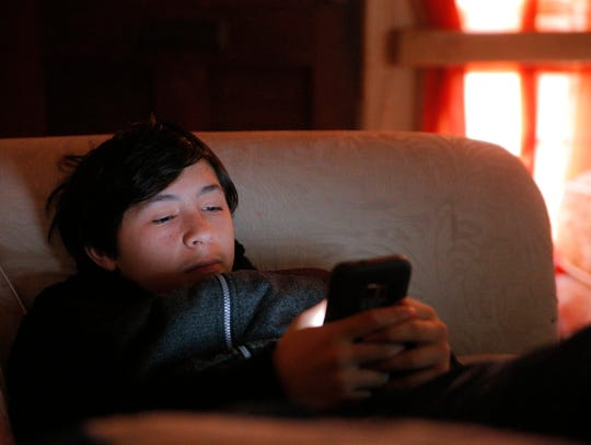 Jose Anzaldo checks his phone before leaving for school