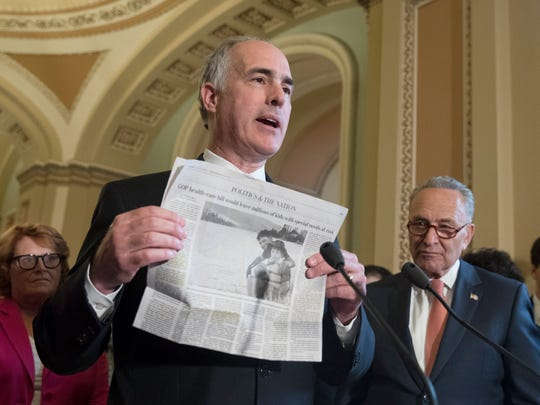 Sen. Bob Casey holds up a copy of The Washington Post