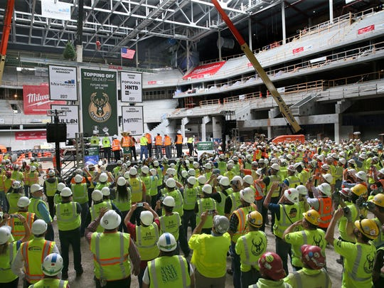 The Milwaukee Bucks hold a topping off ceremony for the new arena.  The final beam in the roof structure is raised into place.  Following tradition, the flag, and a tree are placed on the beam as well.  Here city, county and Milwaukee Bucks leaders watch the beam raised along with all the construction workers on the project.