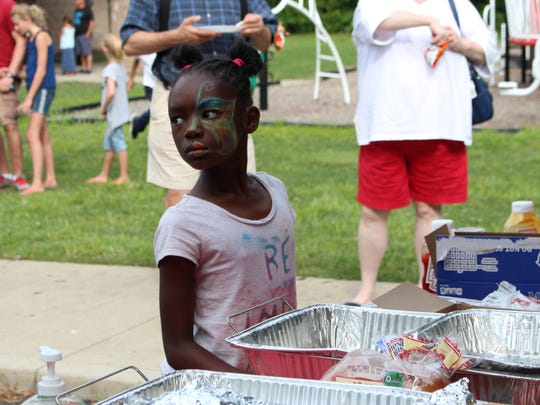 A girl waits in line during NECIC's 10-year anniversary celebration at North Lake Park on Sunday, Aug. 27, 2017. Dozens of community members attended the celebration.