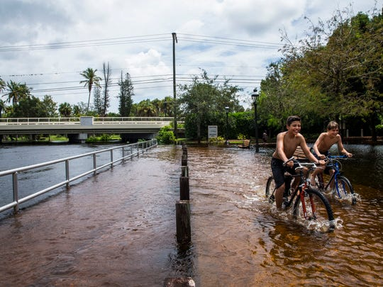 Jack Cannon, 14, right, and Salvador Figueroa, 13, both of Bonita Springs, ride their bikes through the flooded walkway in Riverside Park in Bonita Springs on Monday, Aug. 28, 2017.