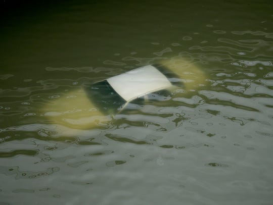A car is submerged on a freeway flooded by Tropical