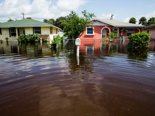 Water floods Pawley Avenue in Bonita Springs on Tuesday, August 29, 2017. The water rose to a few feet in certain places along the street, forcing many families to leave their homes.
