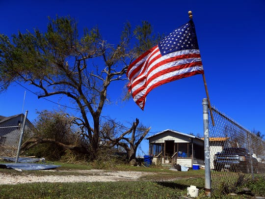 A flag waves near a home on Tuesday, Aug. 29, 2017, in Bayside, Texas. Hurricane Harvey struck the Texas Coastal Bend as a Category 4 Friday, August 25, 2017.