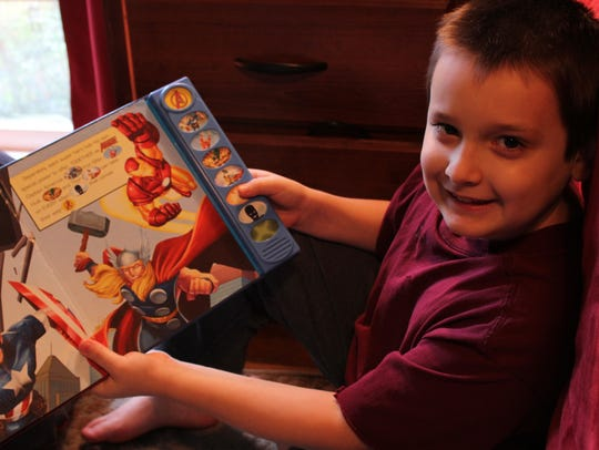 Nathan Englade, 8, holds a book he picked up from Centenary's