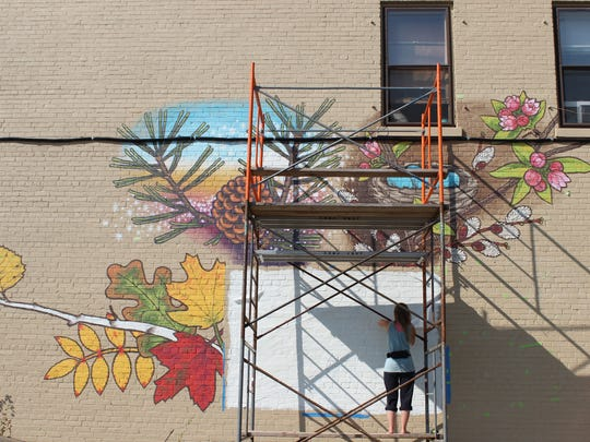 Jessica Kopecky works on a mural on the side of the