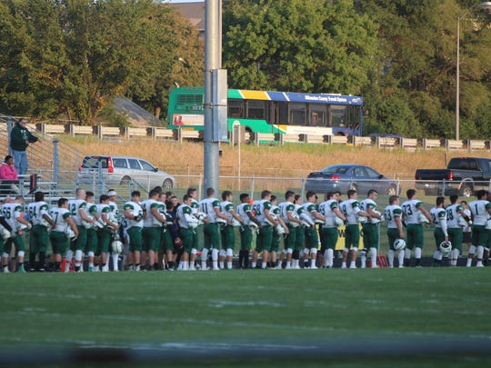 Port Washington football players stand for the national anthem as traffic zips by on Highway 43 overlooking the Nicolet High School football field Sept. 1.