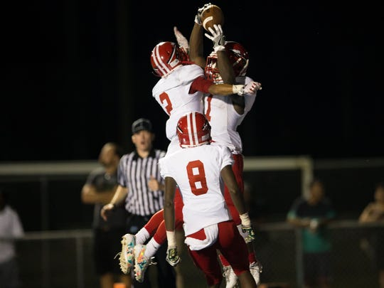 Immokalee's Fred Green (1) celebrates with Nathaniel Betancourt (2) and Jordan Hall (8) after scoring in the second half Barron Collier High School Wednesday, September 6, 2017 in Naples.  The score would put Immokalee up for good to defeat Barron Collier 48-40.