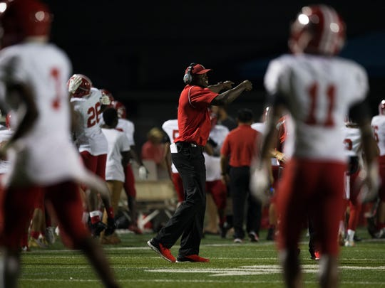 Immokalee High School head football coach Rodelin Anthony celebrates with his team after defeating Barron Collier High School 48-40 Wednesday, September 6, 2017 in Naples.