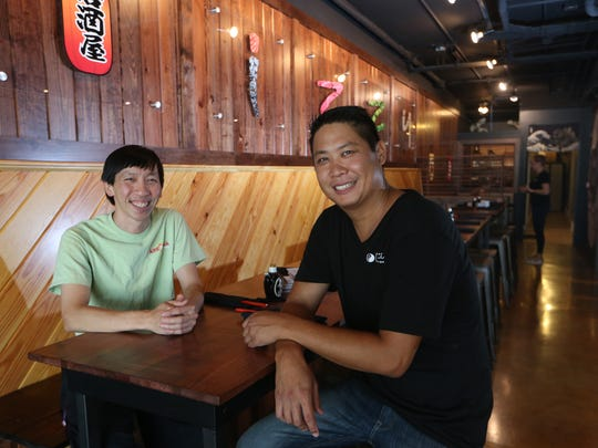 Brothers Viet, right, and Nam Vu, owners of several local restaurants sit inside Izzy's Pub & Sushi, one of their establishments in June.