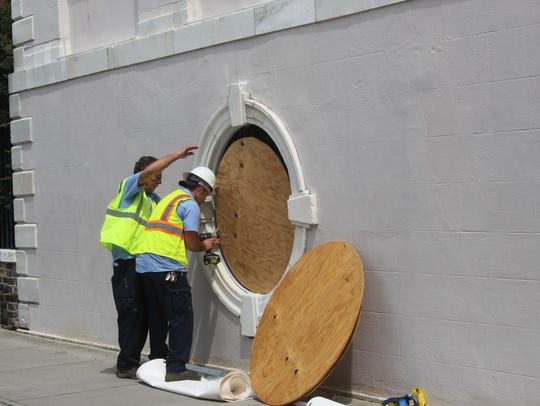 Workers place plywood over a window of Charleston City