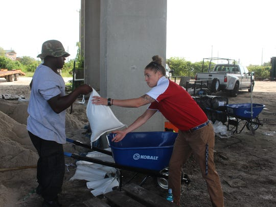 Charleston resident Emily Pohl takes a sand bag from