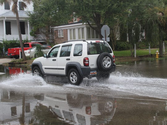 A vehicle drives on a flooded street in Charleston on Saturday morning.
