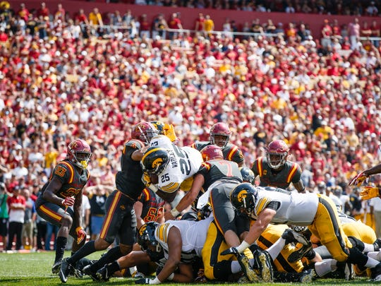 Iowa senior running back Akrum Wadley (25)  jumps the pile for a touchdown during the first half of their football game at Jack Trice Stadium on Saturday, Sept. 9, 2017, in Ames.
