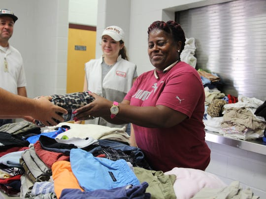 Red Cross volunteer Sharon Hill hands out clothing to Hurricane Irma evacuees at a Red Cross shelter in Lawton Chiles High School Saturday.