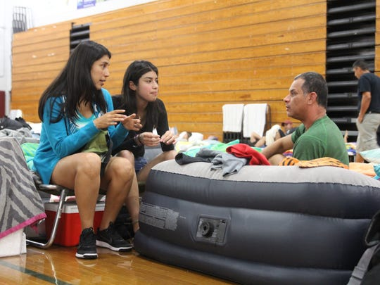 Miami evacuee Gloria Llerena (left), 41, talks with