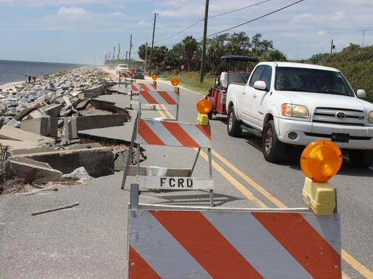 Cars drive past damage from 2016's Hurricane Hermine to escape the path of Hurricane Irma. A mandatory evacuation was issued on Franklin County's barrier islands and low-lying areas.