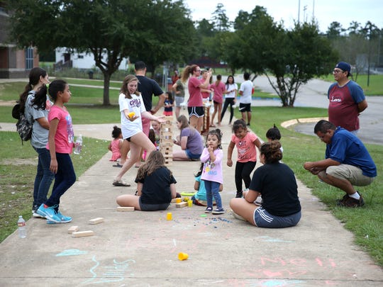 Children play games or run around while adults gather in clusters outside the Red Cross shelter at Chiles High School Saturday. As of Saturday afternoon the shelter had reached its 400 person capacity, and was redirecting evacuees to other shelters.