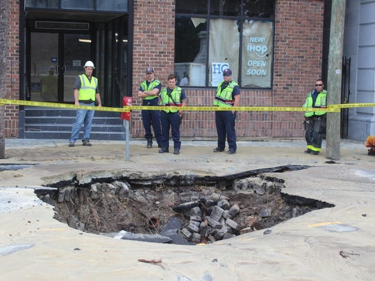 Charleston city workers gaze at a large sinkhole that formed Sunday afternoon on East Bay Street after a water main broke.