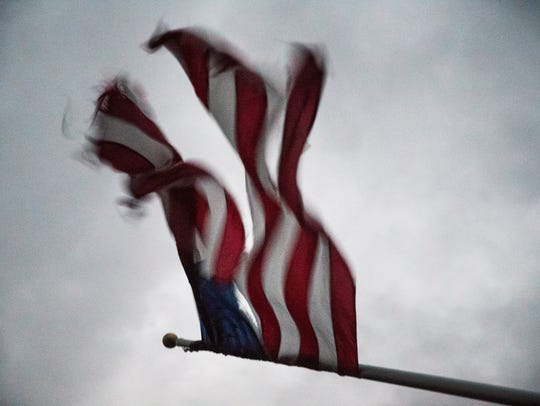 A torn American flag blows in the intense wind following