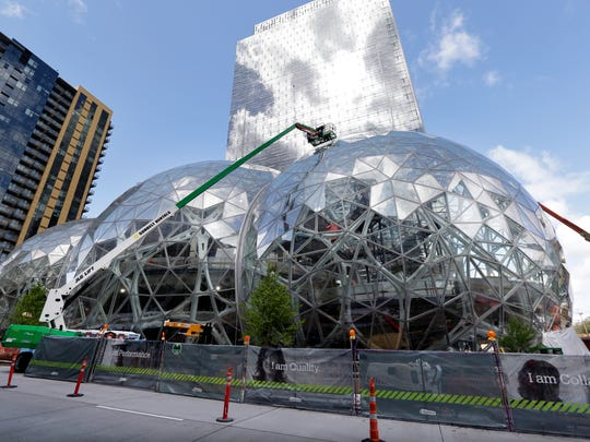 Three large, glass-covered domes are as part of an expansion of the Amazon.com campus in downtown Seattle. Amazon said it will spend more than $5 billion to build another headquarters in North America.