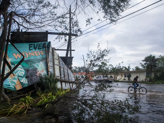 A cyclist rides past the iconic Everglades Wonder Gardens sign, damaged by Hurricane Irma, in downtown Bonita Springs on Monday, Sept. 11, 2017.
