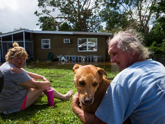 Kelvin and Bobbi Hayes sit with their dog Marley as they wait for the floodwater from Hurricane Irma to drain from their house in Bonita Springs on Monday, Sept. 11, 2017.