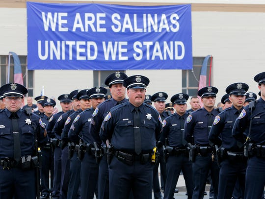 Salinas police officers stand at attention during the