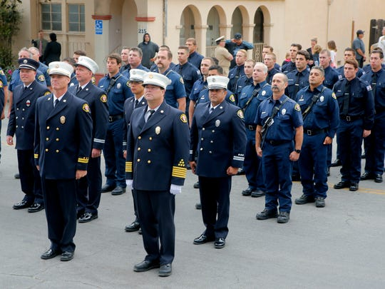 Salinas Fire Chief Ed Rodriguez (center) stands at attention with firefighters at the Sept. 11 ceremony.