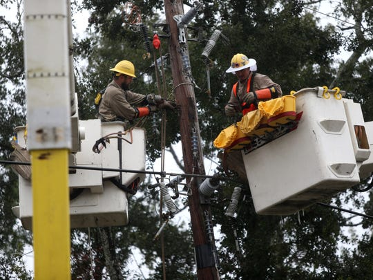 COT linemen Keith Kirkpatrick (left) and Adam Harrison work to restore power after a tree knocked out lines on Mahan Road Monday.