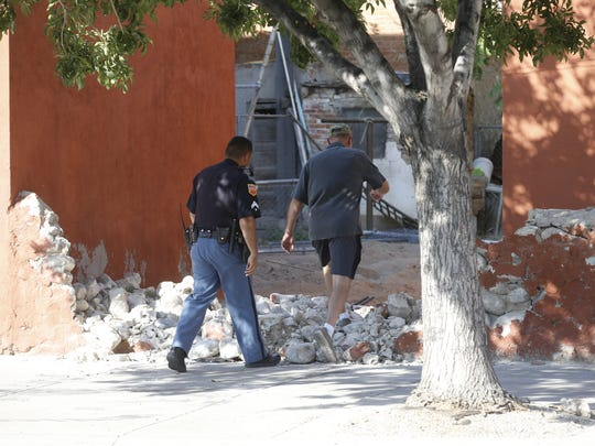 A police officer and Doug Yost, a historic preservationist, walk through one of the holes left by demolition crews Tuesday in a Duranguito property. They started to tear down several buildings Tuesday morning despite a court order.