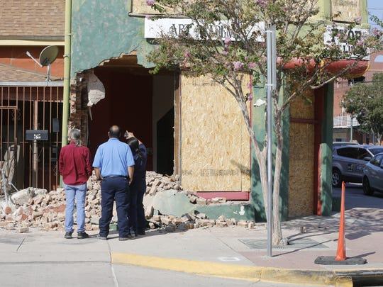 City inspectors look at the damage done to one of the Duranguito buildings after demolition crews started to punch holes in them Tuesday morning, despite a court order.
