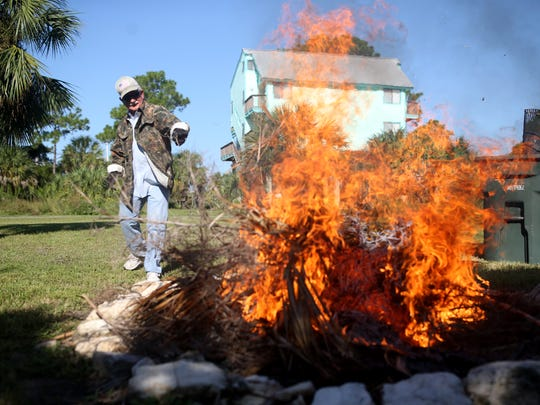 Larry Hess burns debris brought down by Irma in his front yard in Shell Post Tuesday.